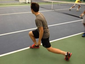 """Players like Regis Liou, 9, do lunges during morning conditioning. Coach Mike Teets runs different drills to prepare his players for the upcoming spring season. """"[Morning conditioning] keeps me in shape during the offseason,"""" said Brandon Peck, 12. Photo courtesy of Alex Wittenbaum."""