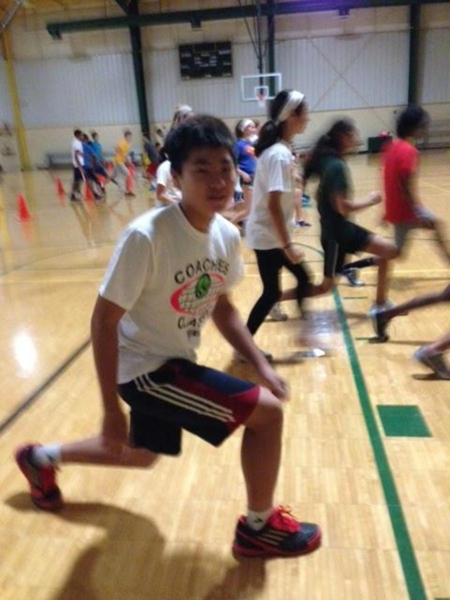 Regis Liou, 9, works hard to train for the upcoming spring season. Behind Regis is the large, hardworking tennis team. The Gregory Center is one of the foundations of the tennis team's success, because they train there.
