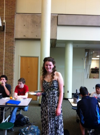 Grace Hertlein, 11 walks around the commons at lunch in a dress provided by Bridal and Formal. She hands out promotional items for local businesses in order to get students excited for Prom. This event is organized by Student Council. Photo Courtesy of Grace Hertlein.