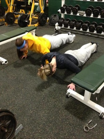 Becca Plaatje, 12, and Liz Izworski, 9, hold a plank in the weight room. Mandatory lifting sessions are held on Tuesday and Thursday mornings at 6:00 a.m. The workouts are designed specifically to focus on areas of the body that softball players often use. Photo Courtesy of Kelly Borman.