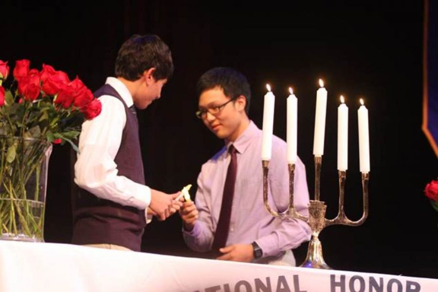 Then-junior+Won+%28Michael%29+Choi+lights+his+NHS+candle+with+the+help+of+graduate+Nicholas+Hershey.+The+NHS+celebration+is+a+regal+event+that+can+take+up+to+three+hours.+Students+gain+valuable+experience+with+volunteering+and+an+award+of+recognition+during+their+time+with+NHS%2C+which+spans+junior+and+senior+year.+