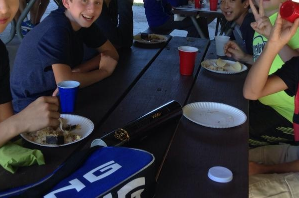 Students enjoy ethnic Chinese food at the picnic. Music plays in the background.