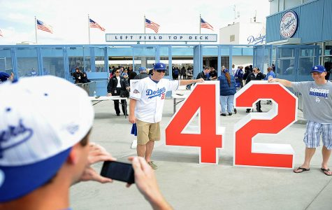 Fans pose with Jackie Robinson's retired number outside of Dodgers Stadium. Robinson played with the Dodgers for 10 years. Robinson's number is retired by every MLB team.