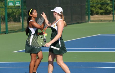Doubles team Sneha Rajagopal and Brianna Dooley congratulate each other after winning a point against the Princeton team.  They do this after every point to emphasize their teamwork and energy.