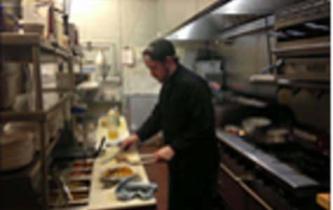 Line cook Sean Pater serves up a meal at Taste of Belgium OTR. The small kitchen is an obstacle, but the team does a great job of getting it done.