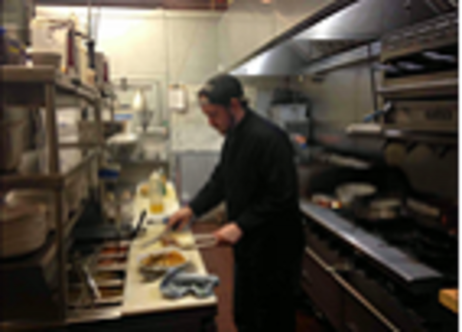 Line+cook+Sean+Pater+serves+up+a+meal+at+Taste+of+Belgium+OTR.+The+small+kitchen+is+an+obstacle%2C+but+the+team+does+a+great+job+of+getting+it+done.+