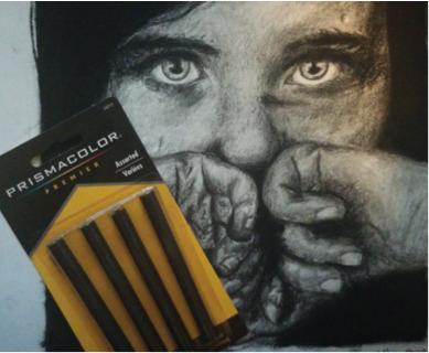 The art piece shown here is done fully with charcoal. It can get pitch black, like on the edges of the piece, or very light and blended, which is shown on the face. Charcoal can come in sticks, like shown, or in pencil form.