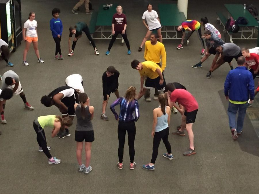 Coach+Hank+Ray+gives+winter+track+athletes+a+New+Year+pep+talk+while+they+stretched.+Seniors+formed+an+inner+circle+of+stretching+while+the+underclassmen+surrounded+them.+The+athletes+have+been+taking+advantage+of+the+revamped+commons+and+have+been+using+it+as+a+makeshift+track.
