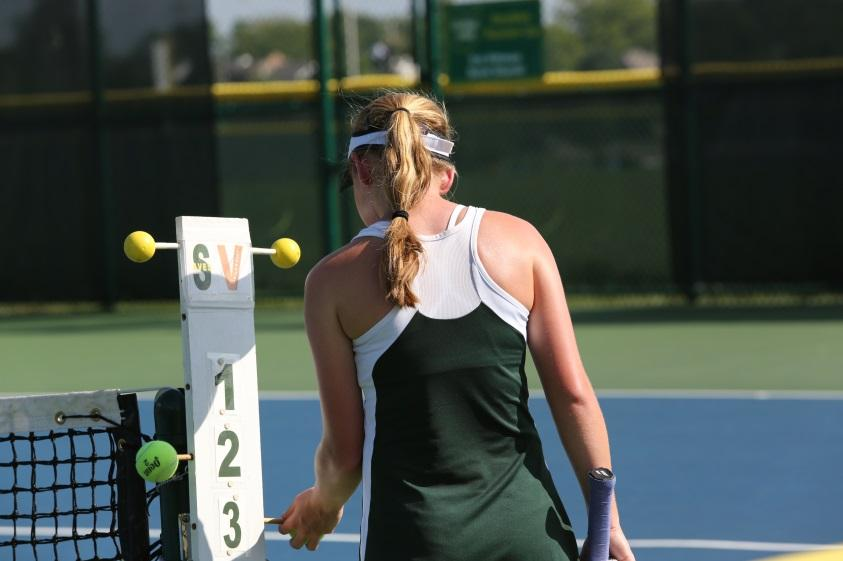 Changing the score for a singles match, junior Alexandra Abele , moves the tennis ball to number three on the score card, signaling the end of the 5th game.  This is a task that either team could take responsibility for after every odd numbered game.