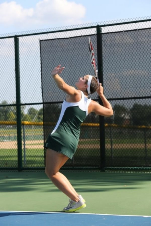 Varsity player, junior, Margaret Skwara, tosses the ball into the air to deliver a powerful serve. The serve can make or break a match, and is an important skill to excel at when it comes to tennis.