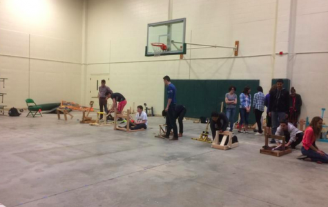 One of the accelerated physics classes tests their catapults in the back gym during class. Students receive one point for getting the beanbag on the board and four for launching the bag into the board's hole. The final winners will be determined on March 27.