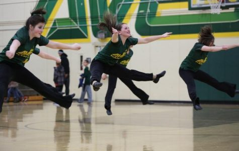 "Freshman Riley Krutz, sophomore Hannah Young, and senior Kathryn Tenbarge toe touches during their half time dance. ""I've been dancing since I was three so I definitely think that helps me pick up the choreography quickly. Also, I am JV football and basketball cheerleader and have been cheering since I was four,"" said Young. Photo courtesy of McDaniel's Photography."