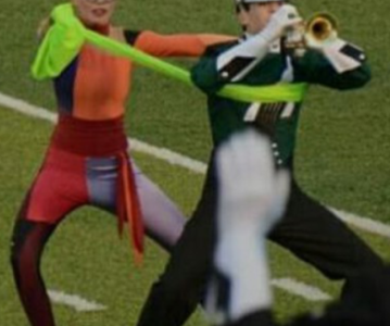 Freshman Lydia Cooke and sophomore Enrique Martin perform in the second movement of the show. The color guard and trumpets do a feature which involves stretchy green fabric. Each member of the color guard is paired with a trumpet.