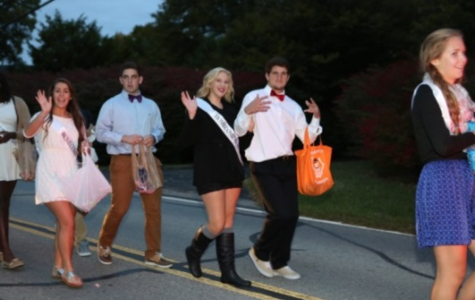 Homecoming court walks in the parade. Seniors Gabriele Kaiser and Gary Traub hand out candy to the crowd. Moving the parade to Friday instead of Thursday is just one of the initiatives to increase school spirit.