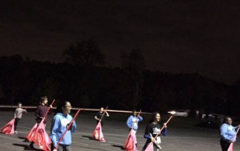 """The guard practices movement three with red shiny flags. This piece will finish off this year's show titled, """"That's a stretch"""". Movement three also has PVC props and features a fast tempo."""