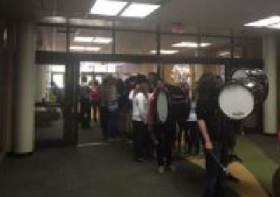 Lead by the drum line, the winning team marches through the school. After walking around the IMC, the procession ends at the front office. Students cheer on the team by lining the hallways.