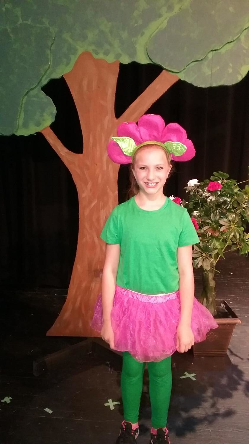 """PICTURE PERFECT. Riley Stauffer, third grader, poses after the final performance of Alice in Wonderland."""" In the musical, Stauffer was one of the flowers during the song, """"Golden Afternoon.""""  She was also in several other songs throughout the show. Photo courtesy of Maddi Saunders."""