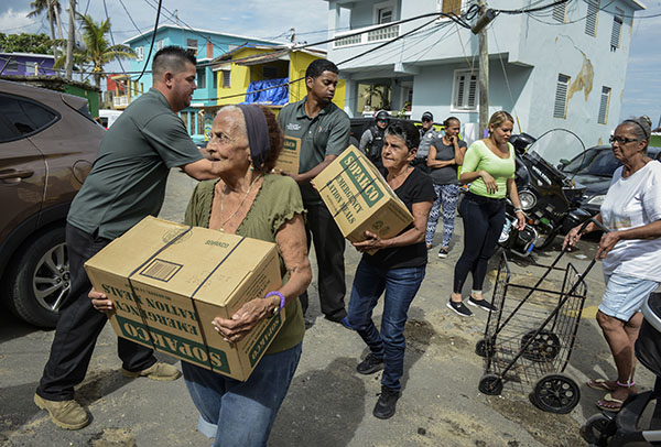 TEAM EFFORT. Hurricane Maria victims receive water and other supplies to sustain themselves. Water and electricity are essentials that parts of the island are still living without. Volunteers and alternative sources of energy are being utilized to aid in recovery.