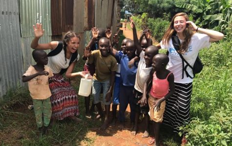 Senior Makayla Stover smiles for a picture with Ugandan children. Stover had the opportunity to go on a trip to Uganda. These children are part of the community of several Uganda children Unified for Uganda helps.