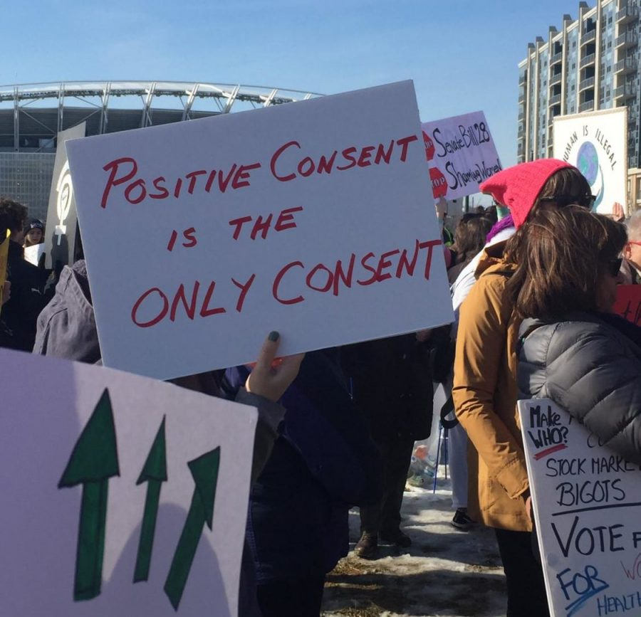 """CONSENT. A participant in Cincinnati's Women's March holds a sign that reads: """"Positive consent is the only consent."""" Sexual assault stories are being shared worldwide via the #MeToo movement, and an exhibition in Belgium featuring victims' clothing worn at the time they were assaulted seeks to cease the belief that clothing determines consent. """"I believe in the power and rights of women, and no matter what someone is wearing, it does not excuse another person's vile actions,"""" said Thea Ferdinand, 12."""