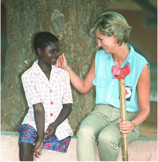"""""""PEOPLE'S PRINCESS."""" Princess Diana meets with a child during her visit to Angola. She was extremely popular for her humanitarian efforts and remains so even after her death. Diana was particularly known for her positive energy and her ability to uplift those around her."""