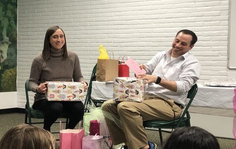 IT'S A GIRL. Assistant coach Stephen Langdon and his wife Carly open up presents gifted from the Varsity swimmers. The Langdons received a variety of gifts ranging from onesies to diapers. The party took place at 4:30 p.m. directly after swim practice in the team room.