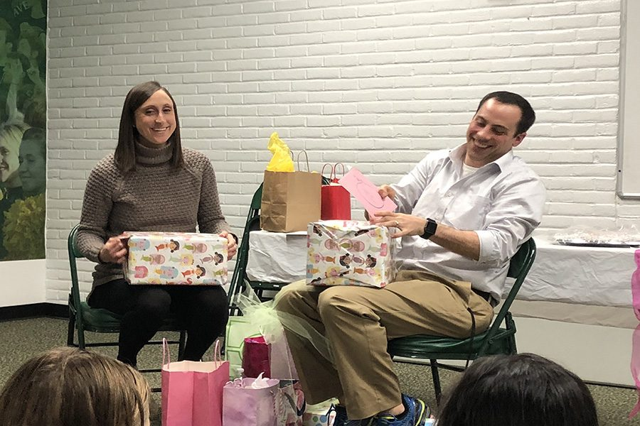 IT%E2%80%99S+A+GIRL.+Assistant+coach+Stephen+Langdon+and+his+wife+Carly+open+up+presents+gifted+from+the+Varsity+swimmers.+The+Langdons+received+a+variety+of+gifts+ranging+from+onesies+to+diapers.+The+party+took+place+at+4%3A30+p.m.+directly+after+swim+practice+in+the+team+room.+