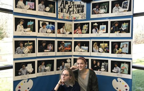POSE. Seniors Emily Chien and Thea Ferdinand show off the opening panel for the AP Studio Art section of the district art show, which opened on March 2. The panel displays photos of all the artists in the studio classes; similar panels were used for the AP 3D and AP Photo students. Each group picked a theme for their panel; for AP Studio, the theme was Bob Ross.