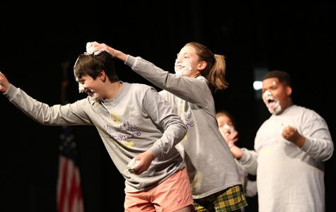 """OKAY TO GET MESSY. Freshman Jozy Allen smears whipped cream on the crown of freshman Noah Pelberg's head. The goal of this game was to find gummy worms in a tin of whipped cream using only one's mouth. """"It sort of turned into a pie fight with Noah Pelberg getting a bunch in his hair,"""" said competitor Jacob Frankel, 11."""