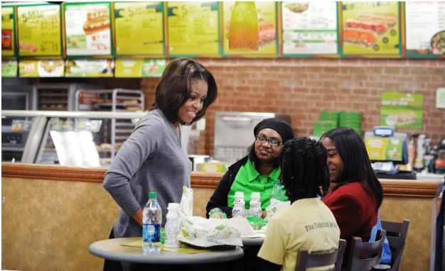 FIRST LADY. Michelle Obama speaks with customers at subway. As a part of her Let's Move campaign Michelle worked to promote healthier eating choices. To this end, she partnered with many businesses including Subway.