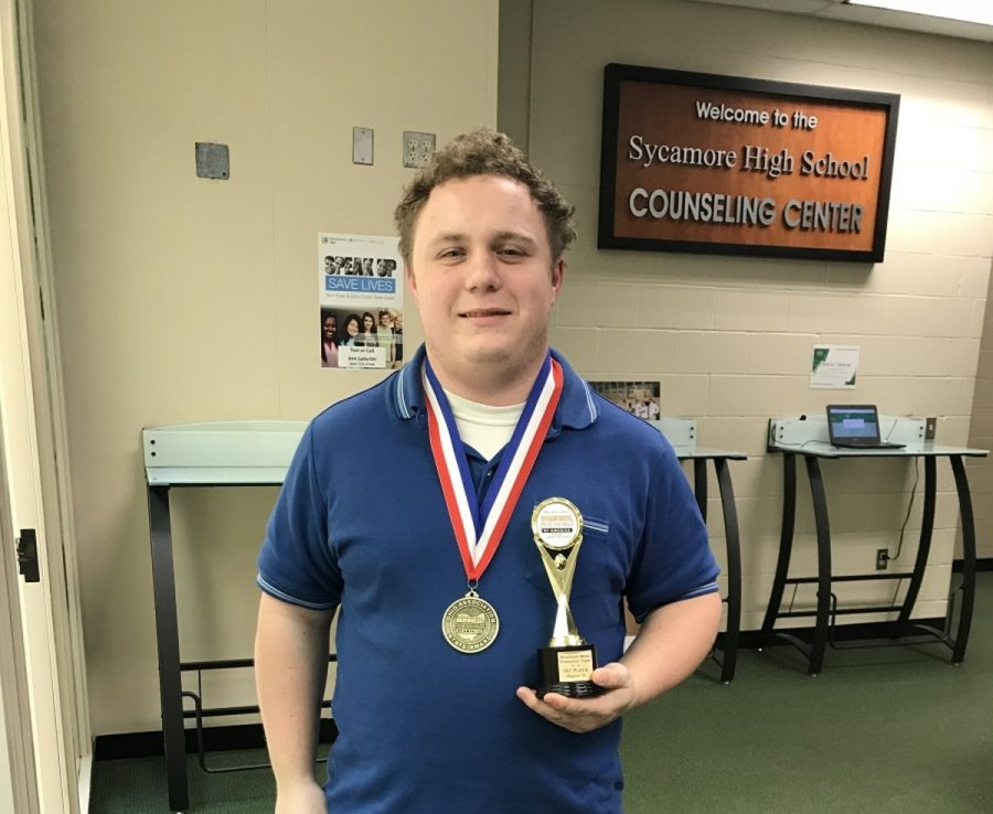 DOMINATE.+Senior+Christopher+Banzhaf+wears+his+medal+from+achieving+sixth+in+state+and+holds+the+trophy+from+first+at+regionals.+Banzhaf+focused+on+sound+editing+and+some+video+editing.+%E2%80%9CWe+all+chipped+in+and+did+it+together%2C%E2%80%9D+Banzhaf+said.+