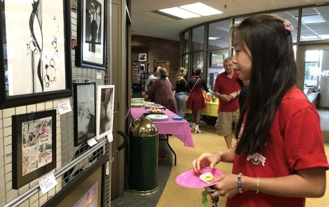 ART GALORE. Senior Kaitlyn Jiang looks at artwork on display at the Senior Art Show on May 4 as she snacks on some of the food provided. The show features pieces created by the AP Studio Drawing, 3D, and Photo seniors. This is their final show at the high school.