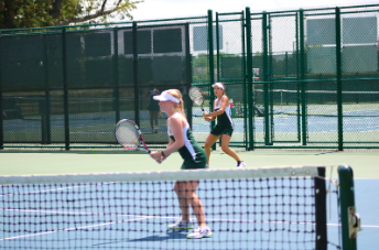 EYES ON THE PRIZE. Seniors Helen Sotropa and Amanda Wilson are pictured whilst playing a focused doubles match from the prior season. The team will notably face longtime rivals Mason on Sept. 4, and continue preparation for the Greater Miami Conference (GMC) tournament as well as the Coach's Classic tournament later in the month.