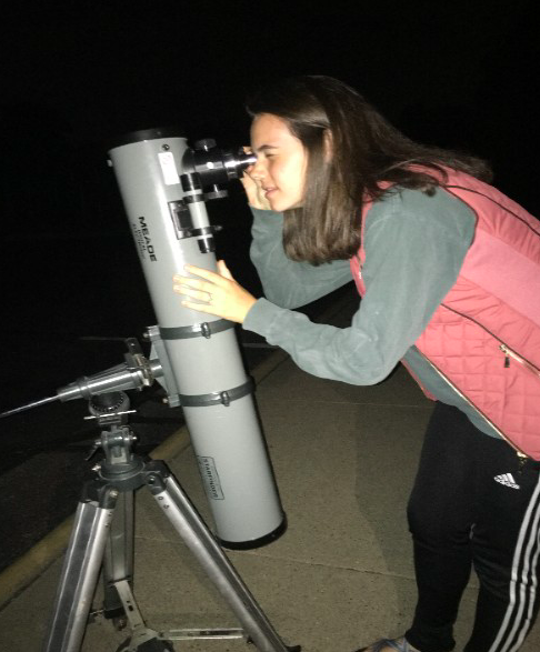 "SEARCHING THE SKY. Astronomy Club president Peyton Gilhart looks through a telescope. Some of the telescopes were brought by science teachers, while others are owned by club participants. The telescopes that were set up at the meeting provided an interesting opportunity for students to see different planets. ""I enjoyed spending my Saturday evening learning about astronomy but having fun with my friends,"" said Sarah Schrantz, 10."