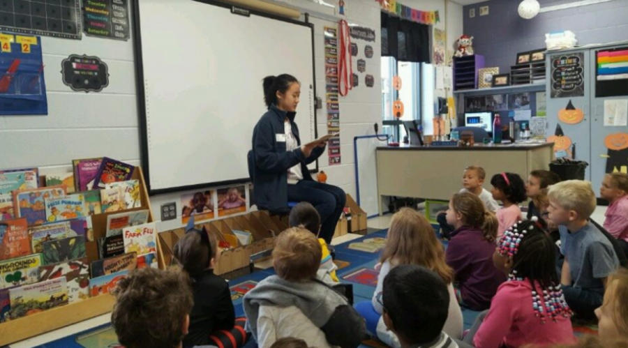 GIVING BACK. Seniors spent the day on Tues., Oct. 16 helping out in various local places. Pictured is senior Hannah Lee reading to a class of first graders at Blue Ash Elementary School. Popular locations were younger grade schools and community organizations such as Matthew 25 Ministries. It is a rewarding experience and lasting memory for both seniors and community members.