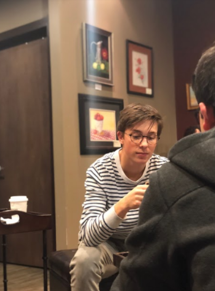 """COFFEE AND CONVERSATION. Junior Grant Kilgard enjoys coffee while practicing his conversational French. """"I think students really like the comradery of learning and speaking French together,"""" said Grant Bruner, 12."""