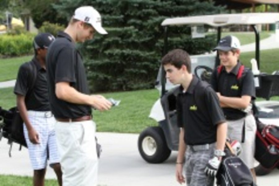 The team arrives at the next hole, as Drew Schneider, 9, steps out of the golf cart.