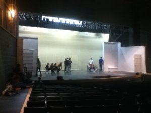 The cast mingle on stage as a microphone sound check takes place. The set (as of Wednesday, Jan. 22) was painted entirely white in preparation for the bright colors of the 1920s. The set features the narrator's apartment, the Grand Hall, the groom's room, the bride's room, and an outdoor set with the appearance of a biplane. Photo courtesy of Tori Swart