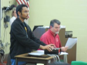 Pavan Nimaganda, 11, handles the buzzers while Coach Clark reads the questions.