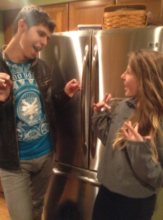 """Siblings, Victoria and Nicholas Schaefer are practicing their sign language skills at home. Victoria is signing to her older brother """"what's up"""" as he responds with the sign for """"nothing"""".  Practicing on your own can help significantly increase your fluency in sign language along with any other languages. Photo courtesy of Lauren Shassere."""