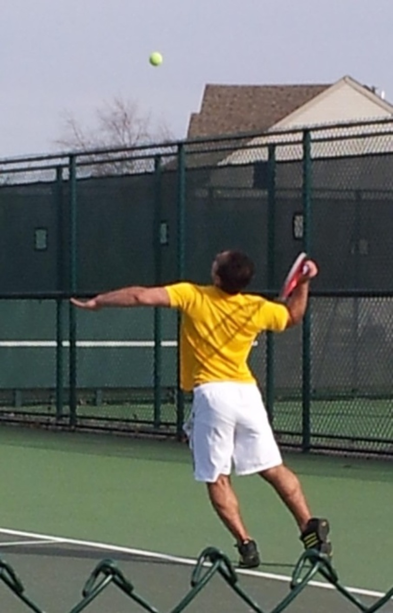 Mustafa Ahmad, 12, serves at the Mason courts. He is playing first doubles with partner Noah Stern, 9. They plan to help lead the team to victory over Mason. (PHOTO BY LINDA STERN)