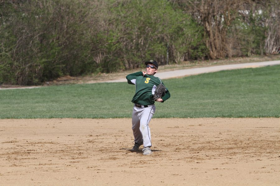 Alex Redwine, 9, fields a ground ball. The team has had a lot of players moving around, with some moving up to JV. Many players have had to adjust to new positions because of the players moving up. Photo Credit: McDaniels Photography