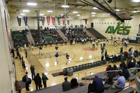 During warm-ups for the Varsity basketball game between Mason and Sycamore on Dec. 20, the Flyerettes perform their sidelines.  The 19 team members go along one side of the basketball court. This line will shrink to 14 next year. Photo courtesy of MCD Photo.