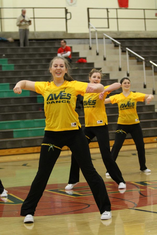 Samantha Weiss, 12 Jennifer Hill, 12 and Lauren Altemuehle, 12 during the winter pep rally. The girls wore their jerseys, underclassmen in green, seniors in yellow. They danced a mix of jazz and hip hop. Photo courtesy of McDaniel's Photography.
