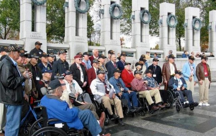 """Members of the 2012 Honor Flight gather around the World War II American Pacific War Memorial in Washington, D.C. The goal of the Honor Flight program is """"To Fly as many World War ll and Korean veterans to see their memorials in Washington DC as we can – as fast as we can."""" The trip is of no cost to the veterans, and special events besides memorial visitations are scheduled throughout the day, including a surprise mail call. Photo courtesy of Mr. Larry Blackmore"""