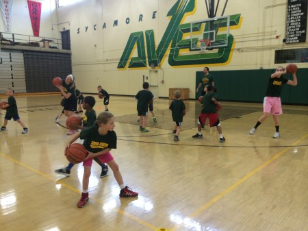 Demonstrating the correct triple-threat position, Taylor Miller, 10 and Erin Kroell, 11, teach a group of 2nd graders how to complete a one-foot pivot. Coaches David Moss and Derek Christerson also lead other drills throughout the one hour session. The first session's focus was  ball-handling, and the coaches and players worked on dribbling skills before applying them in game situations. Photo Courtesy of Lauren Saxon.