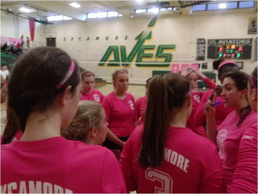 The+Girls+Varsity+Volleyball+team+gathers+around+for+a+team+huddle+during+the+Volley+for+the+Cure+game.+The+team+played+against+Mason.+Students+filled+the+stands+with+pink+to+support+breast+cancer+victims.+