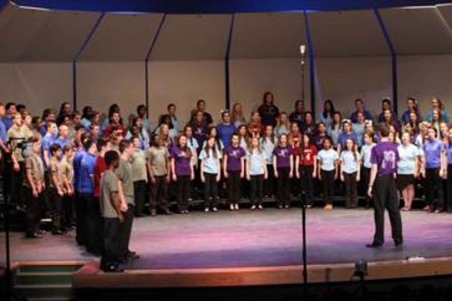 All+the+combined+choirs+together+on+stage+at+a+concert.+Their+director%2C+Mr.+Kenneth+Holdt%2C+is+standing+in+front+of+them.+The+photo+was+taken+during+the+2013-14+choral+season+and+includes+all+the+different+choirs+combined+on+stage.