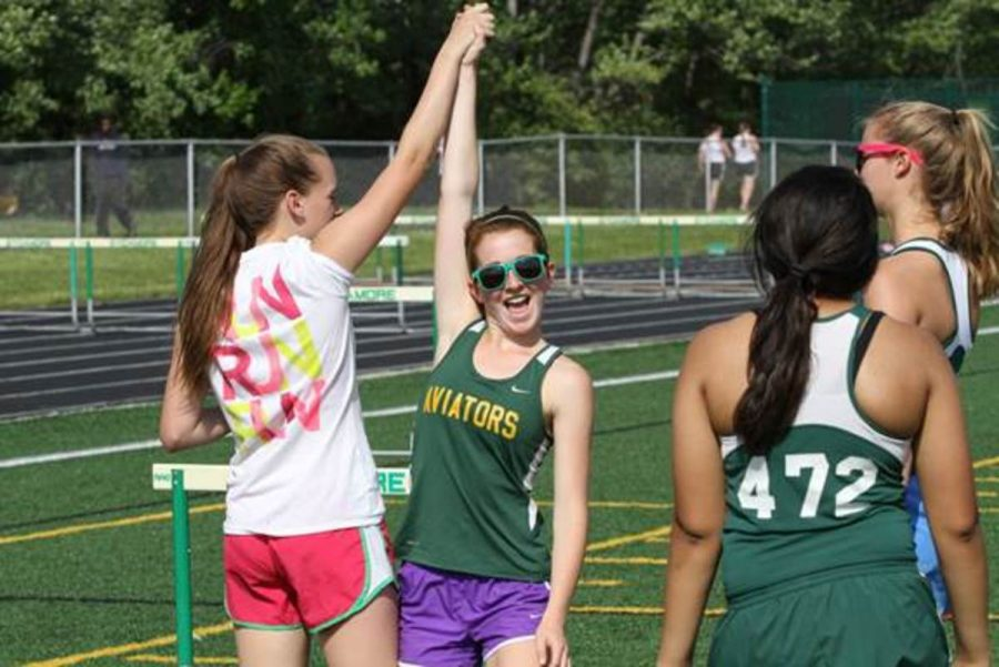Last years freshman and returning track member Tori Bell ,celebrates with her team after a successful race. Throughout her freshman season Bell learned much regarding high school competition.