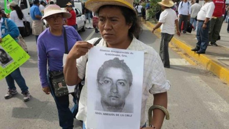 A+protester+in+Mexico+carries+a+picture+of+one+of+the+missing+students.+Guerrero%2C+the+state+where+they+went+missing%2C+has+the+highest+number+of+murders+in+the+country+per+every+100%2C000+people.+The+governor+of+the+state+recently+resigned+due+to+the+protests.